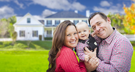 Happy Young Family With Baby Outdoors In Front of Beautiful Custom Solar Panels